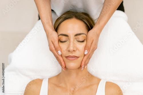 Fotografie, Obraz Middle-aged woman having a head massage in a beauty salon.