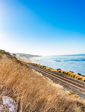 Railroad Tracks Along The California Ocean With Fog And Bright Blue Sky