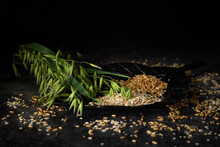 Still Life Of Oats With Ears And Corn On A Black And Rustic Leave, Dark And Moody Food Photography With Black Background