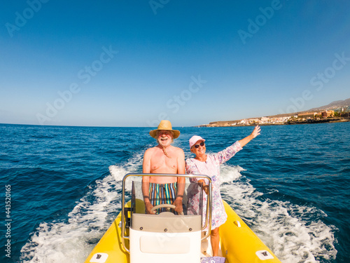 Fotografie, Obraz Beautiful and cute couple of seniors or old people in the middle of the sea driving and discovering new places with small boat