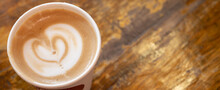 Table Top View Of A Paper Cup Of Hot Latte Coffee On Wooden Table. A Latte Is A Coffee Drink Made With Espresso And Steamed Milk.