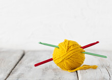 Yellow Yarn Ball And Crochet Hook On White Wood Table