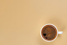 A Cup Of Freshly Brewed Coffee With Hearts Inside On A Beige Background.