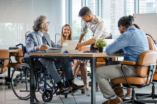 Carta da parati Happy businessman in wheelchair reading documents during a meeting with his colleagues in the office