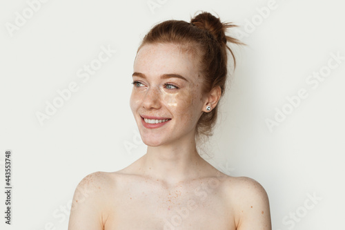 Adorable ginger woman with freckles is smiling on a white studio wall wearing tr Fototapet