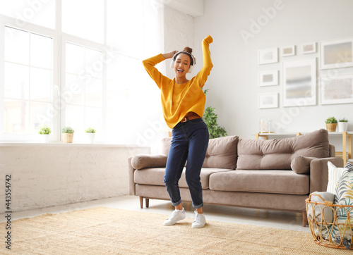 Cuadros en Lienzo Young playful african american woman in headphones jumping and dancing in living