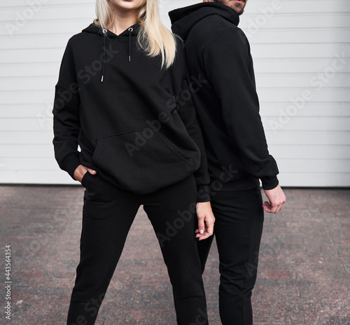 Fotografie, Obraz Woman stands in black no logo hoodie with bearded man behind her