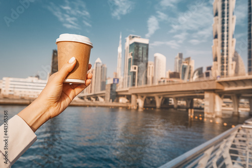 Slika na platnu Hand with delicious coffee in paper cup at the Dubai Canal embankment with tall
