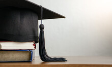 Graduation Cap.Mortar Board With Degree Paper And Books On Wood Table. Graduation Concept.