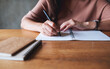 Closeup image of a woman writing on a blank notebook on wooden table