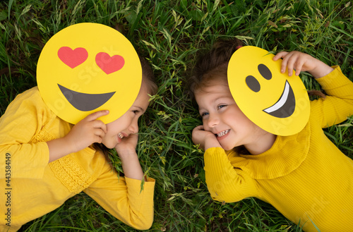 Two funny little girls are lying on the lawn covering part of their faces with emoticons and laughing merrily. World emoji Day. Anthropomorphic smile Face.