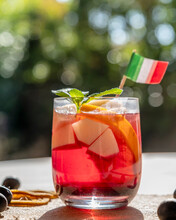 A Tasty Glass Of Sangria With Pieces Of Fruit Inside In Backlight