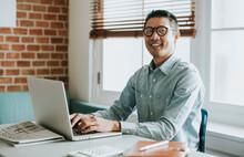 Asian Businessman In An Office Using A Laptop