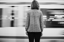 Rear View Of A Blond Woman Waiting At The Train Platform