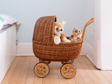 Plush Toys In Wicker Doll Pram Set On Hardwood Floor, With Pale Blue Bedroom Wall