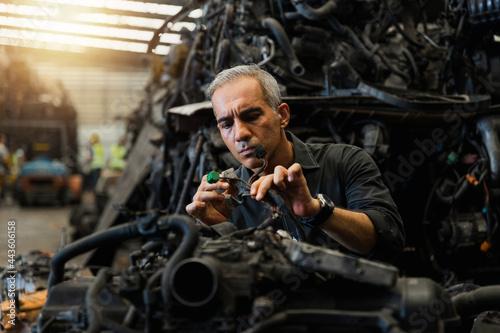 Attractive man working hard and fix Auto mechanic on car engine in mechanics garage. Repair service