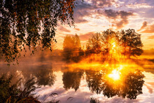 Misty Sunrise On The Pond In The Autumn Morning. Birch Trees With Rays Of The Sun Cutting Through The Branches, Reflected In The Water.