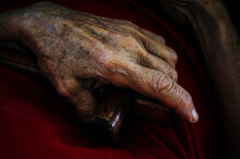Close-up Of Elderly People Holding A Red Cross