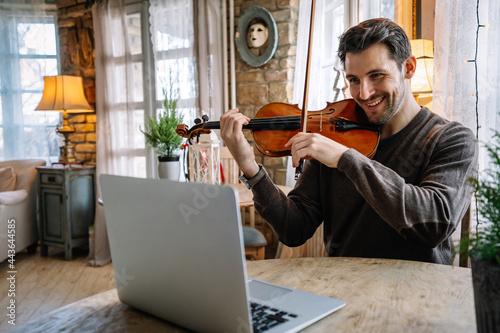 Obraz na plátně Man student learns to play the violin online using a laptop.