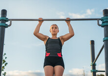 Woman Athlete Doing Pull Ups On A Bar Outdoors
