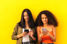 Afro And Caucasian Women Watching Mobile Leaning On A Yellow Wall