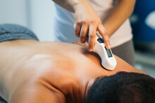 Anonymous Therapist Using Ultrasound Applicator On A Patient Back