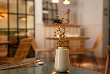 Vase With Dried Plants On Table In Restaurant