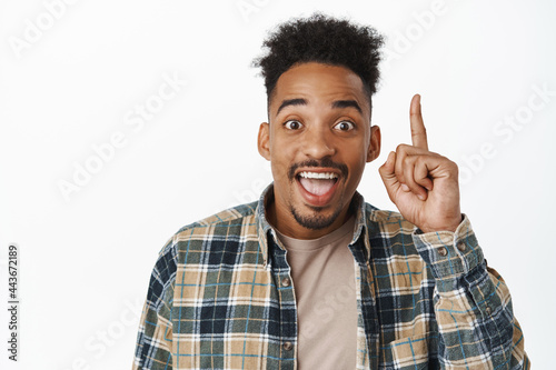 Canvas Print Portrait of happy african american guy saying great news, raising finger up and
