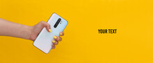 Woman Hand Holding Modern Smarphone On Yellow Background. Copy Space
