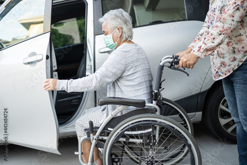 Murais de parede Help and support asian senior or elderly old lady woman patient sitting on wheelchair prepare get to her car, healthy strong medical concept