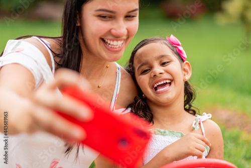 Slika na platnu Primer plano de madre e hija muy sonrientes tomando un selfie con un celular roj