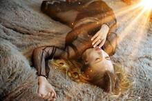 The Girl Lies On The Bed In Bright Light