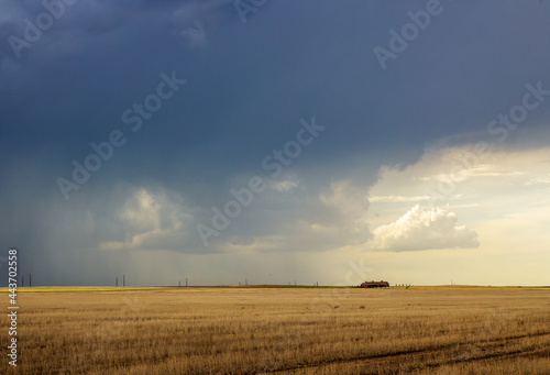 Fotografie, Obraz Dark storm clouds over the horizon with heavy rain on a windswept prairie, sunlight, and a farm house in the distance