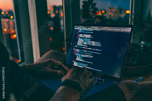 The code is on a laptop on a wooden table in front of the window in the dark with a view of the lights of the night city, color lighting in the room, home decor