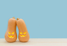 Halloween Day. Two Cute Pumpkins With Funny Faces Stand On A Blue Background. Holiday Party. Trick Or Treat. Greeting Card Or A Banner For A Store Sale. Copy Space.