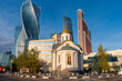 A small orthodox church in front of modern towers in Moscow City, Russia