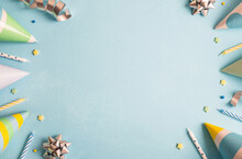 Birthday Party Background. Carnival Caps, Confetti, Streamers And Candles On Pastel Blue Surface. Top View, Flat Lay, Copy Space, Frame
