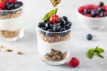 Honey Is Poured On Granola With Yogurt, Blueberries And Raspberries. Healthy Breakfast. Menu, Recipe.