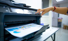 Office Worker Prints Paper On Multifunction Laser Printer. Copy, Print, Scan, And Fax Machine In Office. Document And Paper Work. Print Technology. Hand Press On Photocopy Machine. Scanner Equipment.