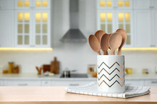 Holder With Spoons On Wooden Table And Blurred View Of Stylish Kitchen Interior. Mockup For Design