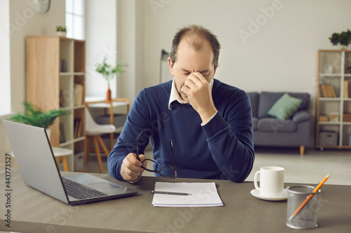 Fotografia, Obraz Senior business man who is tired from the workload suffers from headaches and lack of sleep