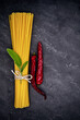 Pasta tied with a ribbon, a sprig of sage and dried chili peppers on a black slate plate - ready to cook
