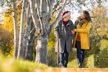 Woman With Grandmother Walking In Park In Autumn