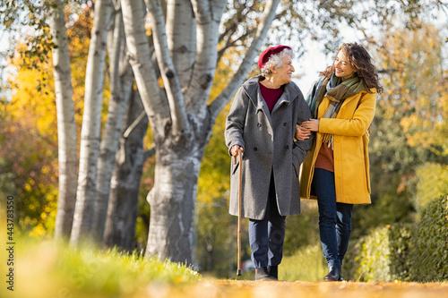 Fototapeta Woman with grandmother walking in park in autumn