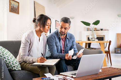 Fototapeta Mid adult couple working on home finance
