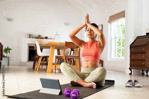 Obraz na plátně Mixed race woman practicing yoga at home
