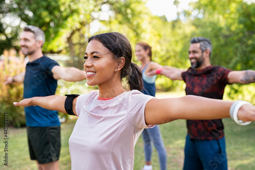 Fotografie, Obraz Mixed race woman exercising in park with mature friends