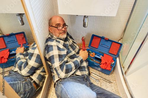 Hausmeister repariert defekten Waschbecken Abfluss