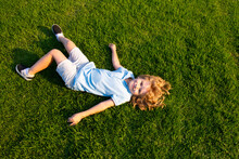 Happy Smiling Boy Relaxing On The Grass. Top View With Copy Space.