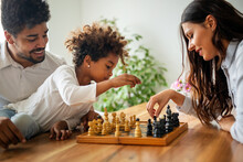 Parents And Child Playing Chess While Spending Time Together At Home. Family Love Education Concept